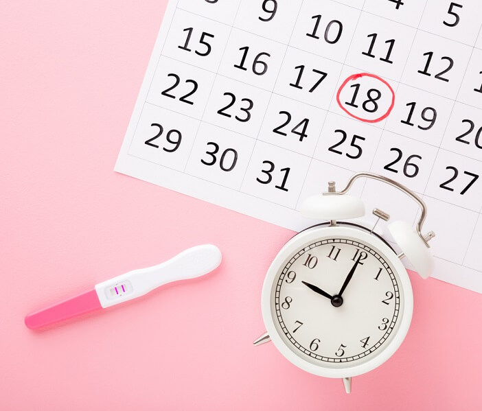 Calendar, clock, pregnancy test on pink background top down