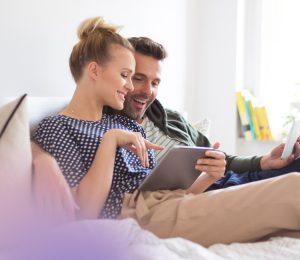Couple sat on sofa looking at an ipad