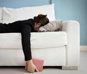 Woman laying face down on a sofa