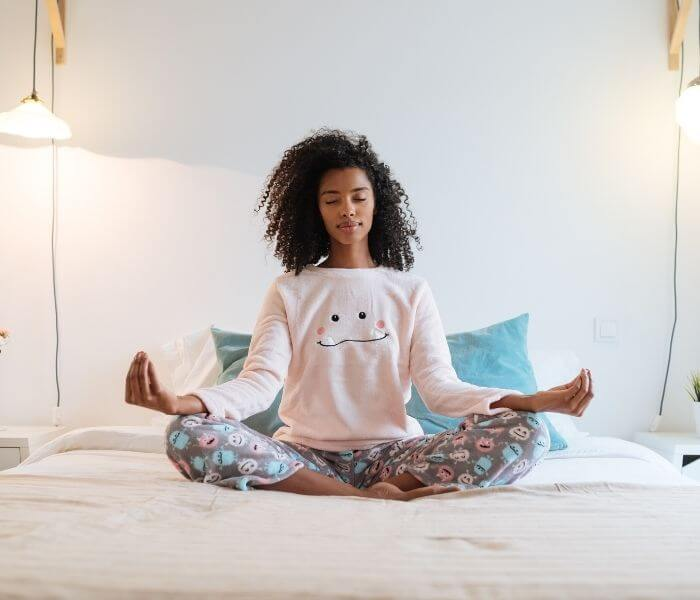woman meditating on her bed