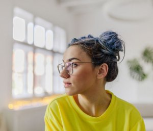 Young woman in yellow top staring out of the window