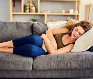 woman on sofa with period pain