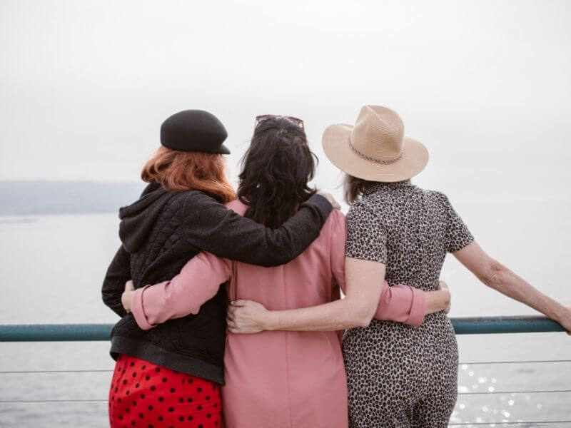 women arm in arm looking out to sea